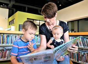 Librarian reading book to young boy and girl